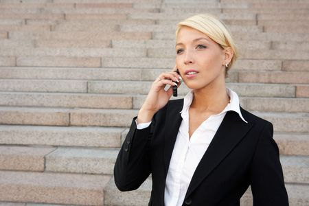 Young businesswoman using mobile phone outside building photo