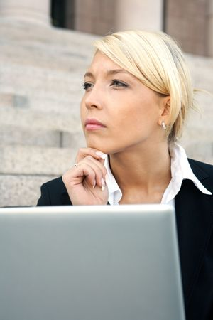 Businesswoman sitting with laptop computer, contemplating photo