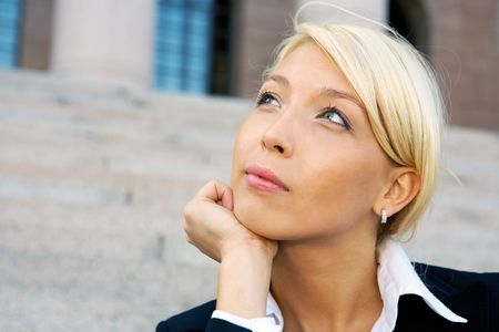 Businesswoman sitting outside building contemplating, close-up photo