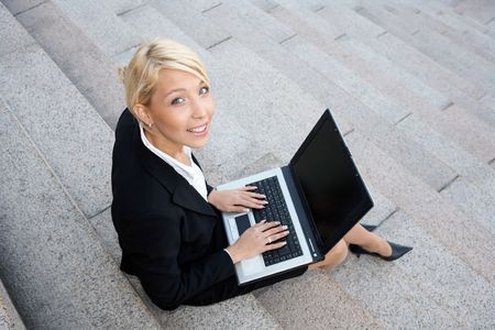 Businesswoman working with laptop computer, looking at camera
