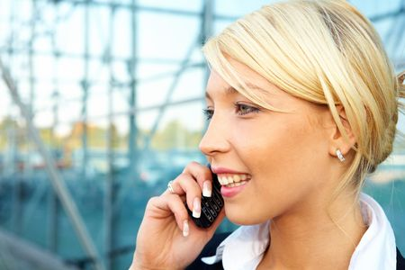Young businesswoman using mobile phone, smiling Stock Photo