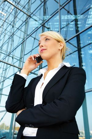 Young businesswoman using mobile phone, looking up Stock Photo