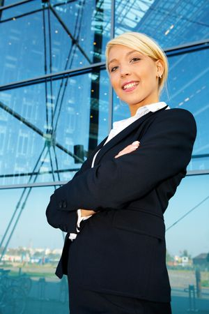Young businesswoman standing by building arms crossed, smiling