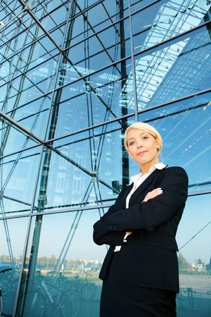 Young businesswoman standing by building arms crossed, wide angle view