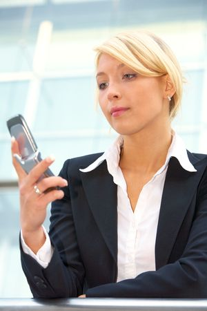 Businesswoman looking at mobile phone, low angle view photo