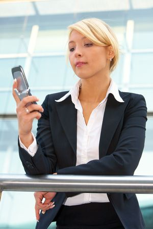 20 25: Businesswoman holding mobile phone, reading message Stock Photo