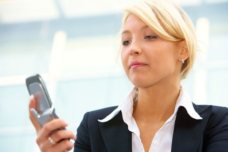 Young businesswoman looking at  mobile phone photo