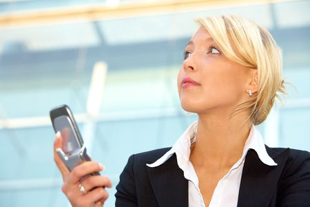 Businesswoman holding mobile phone, contemplating Stock Photo - 3505339