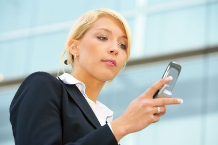 Businesswoman text messaging with mobile phone Stock Photo