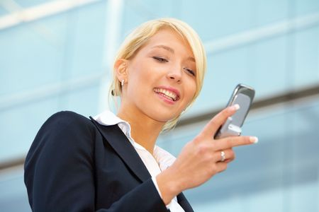 Businesswoman looking at mobile phone, smiling photo