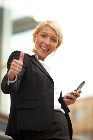 Young businesswoman looking at camera outside office building, showing thumbs up sign