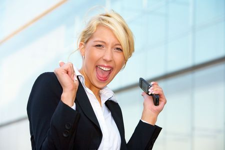 Young businesswoman looking at camera outside office building, holding mobile phone Stock Photo