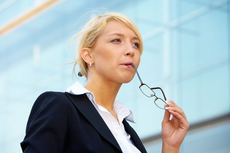 Young businesswoman contemplating outside office building, holding eyeglasses