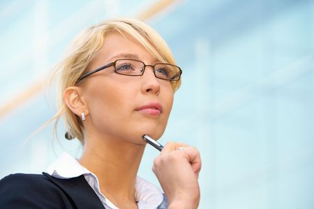 Young businesswoman holding pen outside office building, contemplating