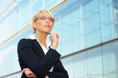 Young businesswoman contemplating outside office building, holding pen Stock Photo