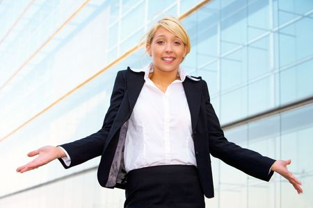Young businesswoman standing with arms open outside office building photo