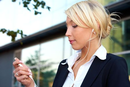 Young businesswoman wearing earphones, holding audio player device