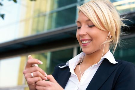 audio player: Young businesswoman wearing earphones, holding audio player device