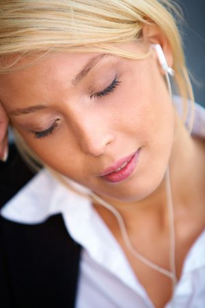 Young businesswoman wearing earphones with eyes closed, close-up photo