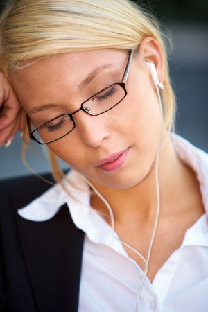 Young businesswoman wearing earphones with eyes closed photo