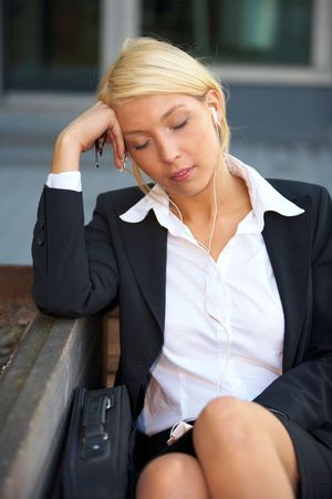 Young businesswoman sitting on bench wearing earphones with eyes closed photo