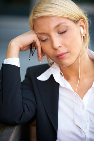 Young businesswoman wearing earphones with eyes closed, holding eyeglasses photo