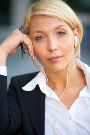 Young businesswoman wearing earphones looking at camera, holding eyeglasses photo