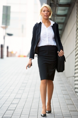formal attire: Young businesswoman walking in city street, looking at camera, holding mobile phone