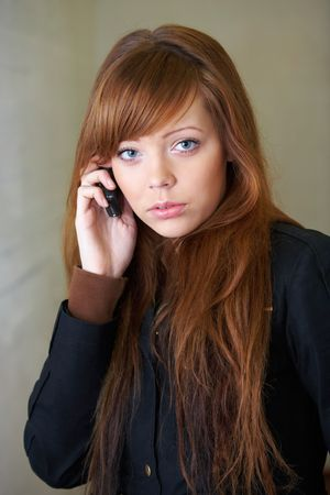 Teenage girl using mobile phone, looking at camera Stock Photo - 3527239