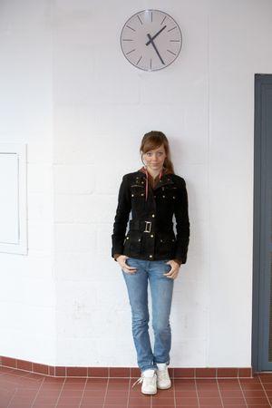 teenaged girl: Teenage girl standing under large wall clock Stock Photo
