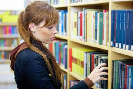 Teenage girl picking up book in library Stock Photo