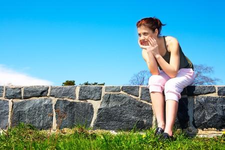 Teenage girl sitting wearing sportswear outdoors Stock Photo