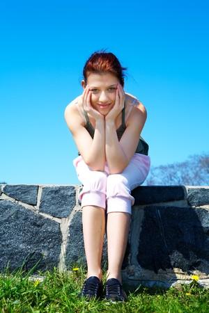 Teenage girl sitting wearing sportswear looking at camera