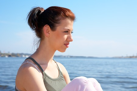Teenage girl sitting by sea on sunny day, looking away Stock Photo