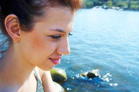 Teenage girl by sea on sunny day thinking Stock Photo