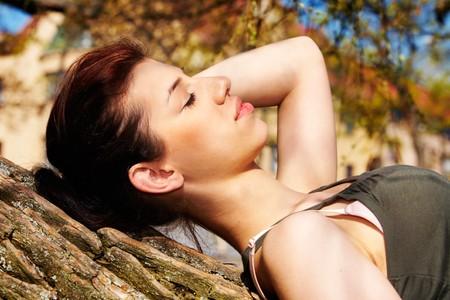 Teenage girl sleeping on tree trunk