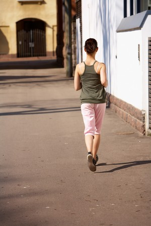teenaged: Teenage girl jogging away on sidewalk in city