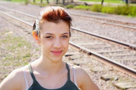 Teenage girl standing by railroad tracks