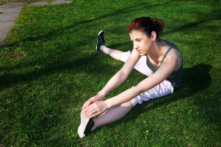 Teenage girl stretching on grass in spring