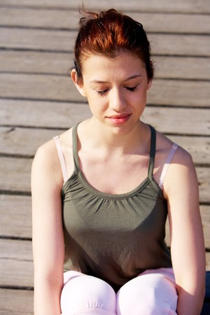 Peaceful teenage girl meditating on pier outdoors