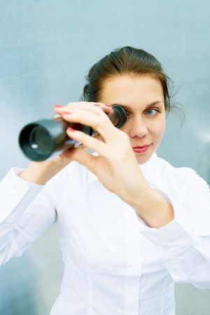 Young woman using telescope outside building photo