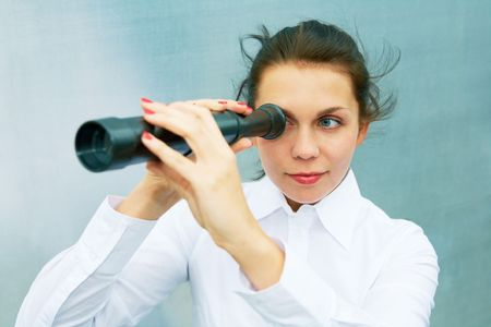 Young woman using telescope beside steel wall photo