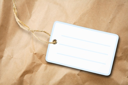 Blank packaging label with cotton string over brown paper photo