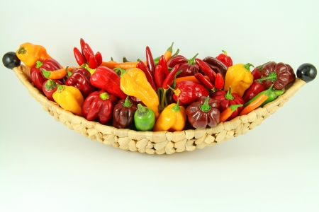 Decorative basket full of colorful chili peppers on isolated background photo