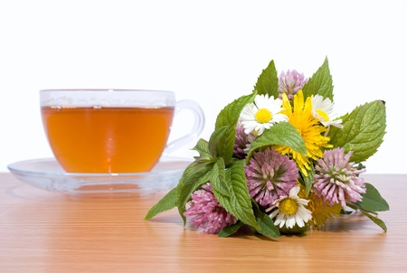 bouquet of herbs with a cup of tea in the background Stock Photo - 19136707