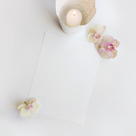 Flat lay composition with orchid flowers, elegant candleholder and blank paper sheet for text or artwork, white background. Light top view photo for business