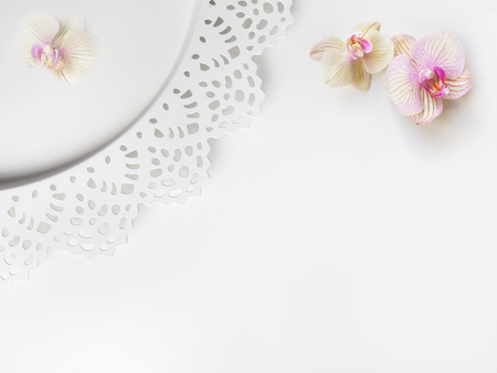 Flat lay composition with orchid flowers, elegant plate and space for text or artwork, white background. Light top view photo for business