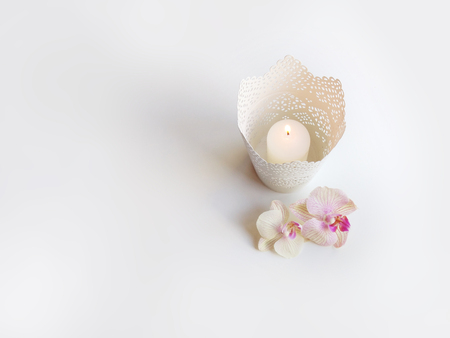 Flat lay composition with orchid flowers, elegant candleholder and space for text or artwork, white background. Light top view photo for business