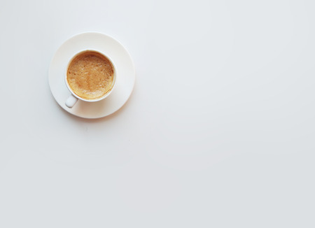 Cup of coffee - top view minimalist composition on a white background