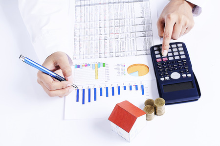loans: Mortgage loans concept with hand working calculator and house paper Stock Photo